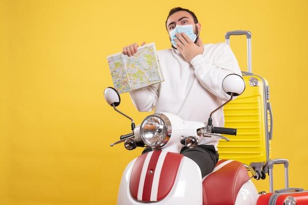 Вид сверху на концепцию путешествия с растерянным парнем в медицинской маске, стоящим возле мотоцикла с желтым чемоданом на нем и держащим карту