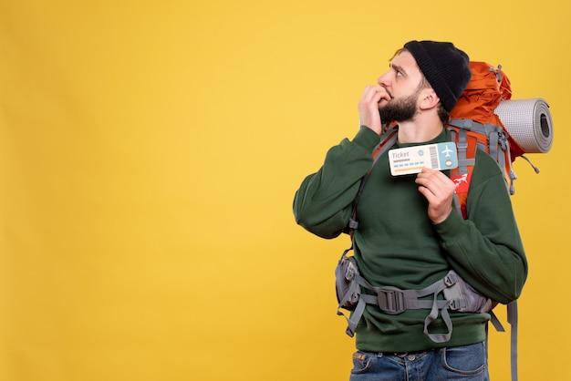 Вид сверху концепции путешествия с запутанным молодым парнем с пакетом и держащим билет