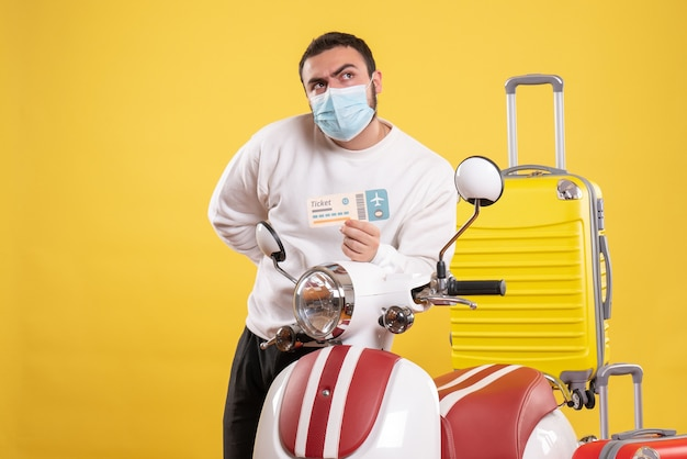 オートバイの近くに立っている医療マスクで好奇心旺盛な若い男と旅行の概念のトップ ビュー