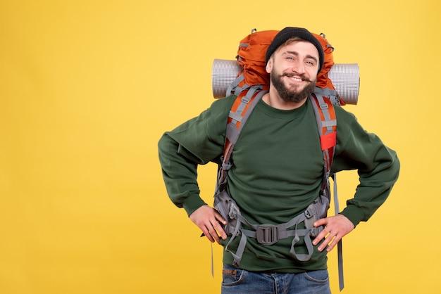 パックパックと笑顔の幸せな若い男と旅行コンセプトの上面図