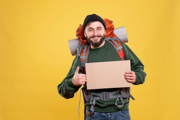 大丈夫なジェスチャーを作るための書き込み用の空き領域を保持しているパックパックと笑顔の若い男と旅行の概念の上面図