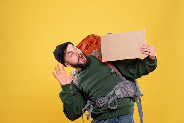 書くための空き領域を保持しているパックパックを持つ驚いた若い男と旅行の概念の上面図