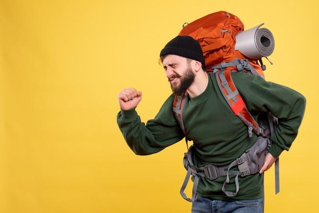 背中の痛みに苦しんでパックパックと問題を抱えた若い男と旅行の概念の上面図