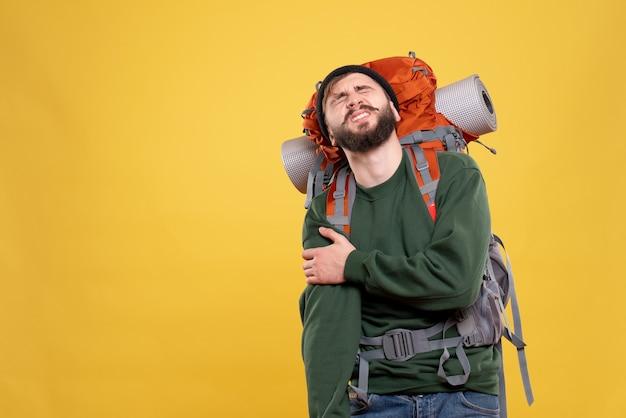 肩の痛みに苦しんでパックパックを持つ問題を抱えた若い男と旅行の概念の上面図