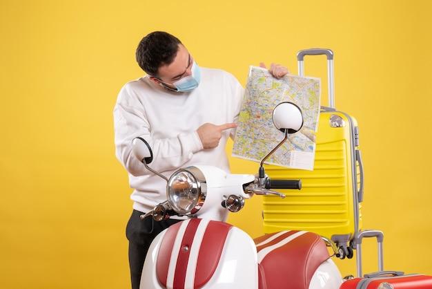 オートバイの近くに立っている医療マスクの若い男と旅行の概念のトップ ビュー
