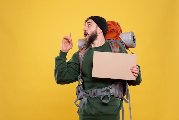 パックパックと上向きに書くための空きスペースを保持している若い男と旅行の概念の上面図