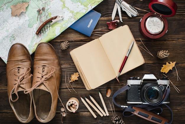 Вид сверху путешествия вещей на деревянном фоне