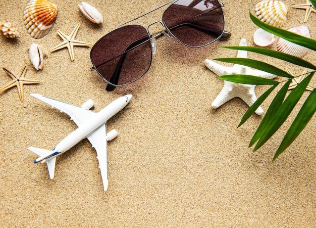 熱帯の砂、貝殻、飛行機の旅行者表面の平面図です。夏休み休暇旅行旅行のための表面。フラットレイアウト、コピースペース