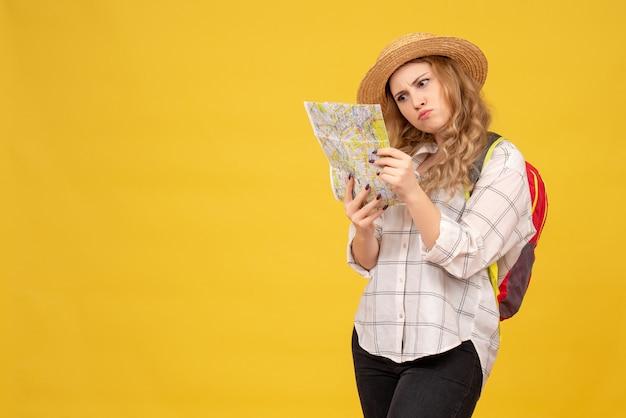 黄色の地図を見ている彼女の帽子とバックパックを身に着けている旅行の女の子の上面図