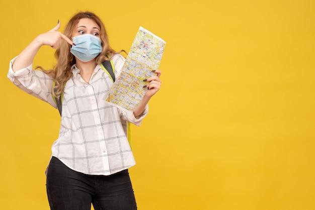 노란색에 그녀의 마스크와 배낭 포인팅지도를 입고 여행 소녀의 상위 뷰