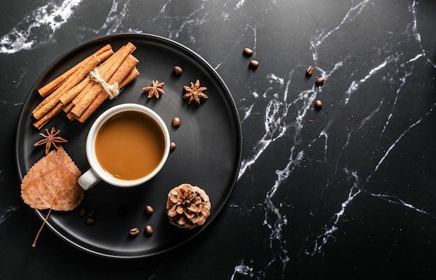 Вид сверху на поднос с чашкой кофе и палочками корицы