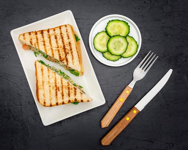 Вид сверху треугольных бутербродов на тарелку со столовыми приборами и ломтиками огурца