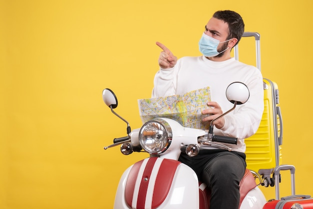Вид сверху на концепцию поездки с любопытным парнем в медицинской маске, сидящим на мотоцикле с желтым чемоданом и держащим карту