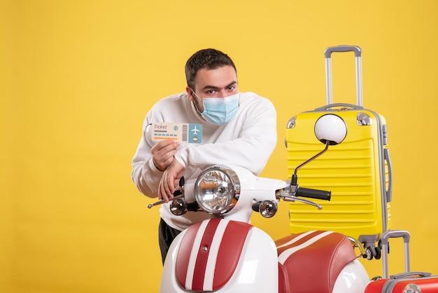 黄色いスーツケースを乗せたオートバイの近くに立ち、チケットを持っている医療マスクを着た男性との旅行コンセプトのトップビュー