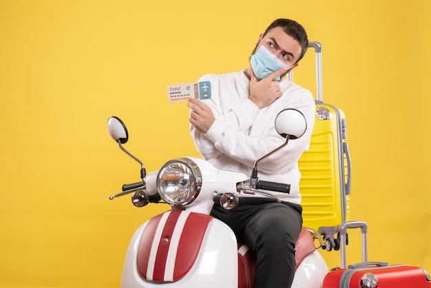 黄色いスーツケースを乗せたオートバイに座ってチケットを持っている医療マスクを着た思考の男との旅行コンセプトのトップビュー