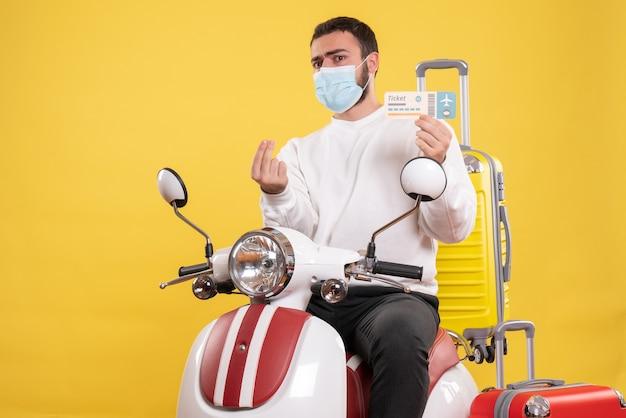 黄色いスーツケースを乗せたバイクに座ってチケットを持っている医療マスクを着た好奇心旺盛な若い男との旅行コンセプトのトップビュー