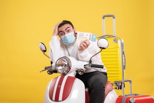 黄色いスーツケースを乗せたバイクに医療マスクを着た若い男が座り、チケットを持って混乱した旅行のコンセプト