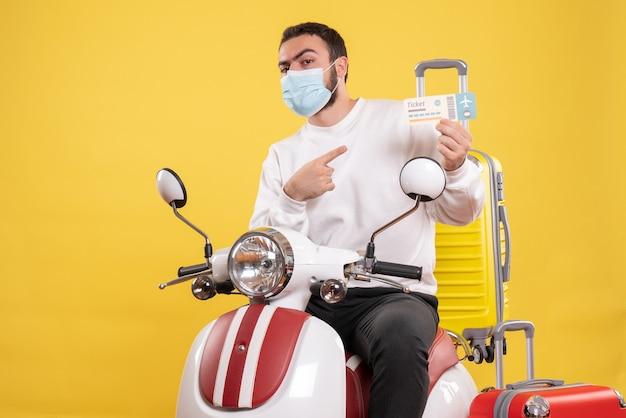 黄色いスーツケースを乗せたオートバイに座ってチケットを指す医療用マスクを着た若い男との旅行コンセプトのトップビュー