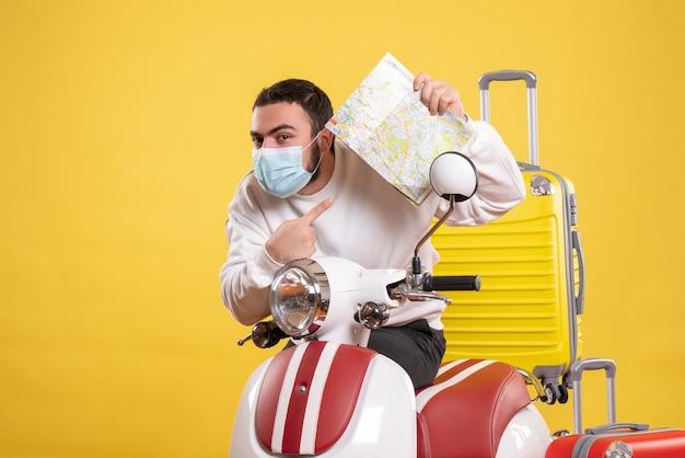 Вид сверху на концепцию поездки с молодым парнем в медицинской маске, стоящим возле мотоцикла с желтым чемоданом на нем и держащим карту, чувствуя любопытство
