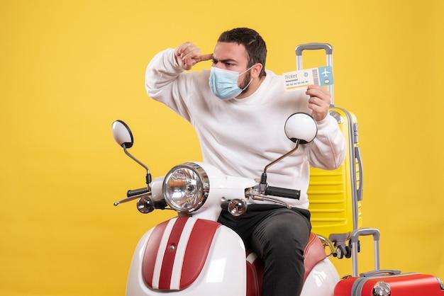 黄色いスーツケースを乗せたバイクに座ってチケットを持っている医療マスクを着た若い思考の男との旅行コンセプトのトップビュー