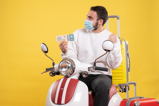 黄色いスーツケースを乗せたバイクに座ってチケットを持っている医療マスクを着た若い不思議な男との旅行コンセプトのトップビュー