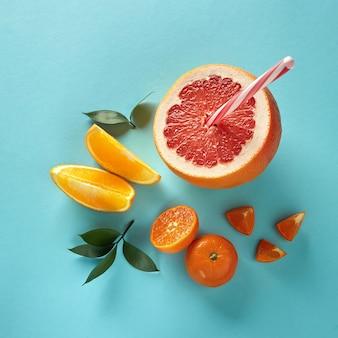 Вид сверху тропических экзотических цитрусовых, половина грейпфрута, мандарин и дольки апельсина с пластиковой соломкой