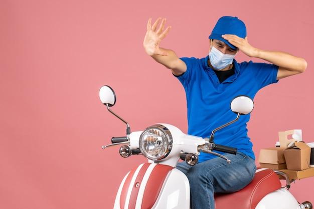 스쿠터에 앉아 모자를 쓰고 파스텔 복숭아에 정지 제스처를 만드는 의료 마스크에 문제가있는 배달원의 상위 뷰