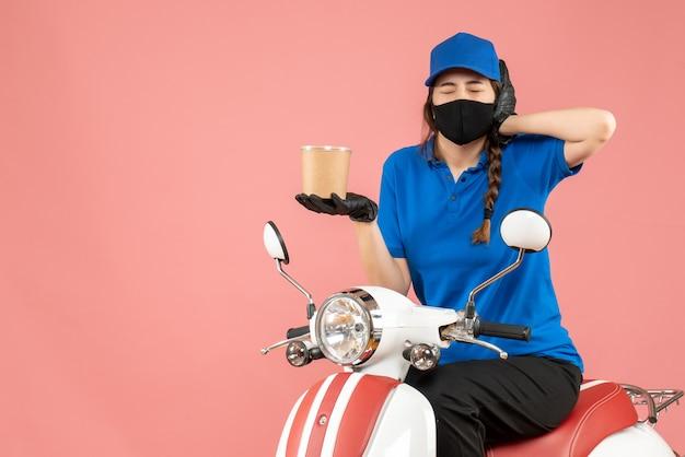 Вид сверху на проблемного доставщика в медицинской маске и перчатках, сидящего на скутере, доставляющего заказы на пастельных персиках