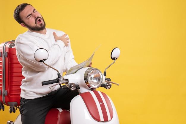 孤立した黄色の背景に心臓発作に苦しんでいる地図を持ってスーツケースを持ってオートバイに座っている問題を抱えた男のトップ ビュー