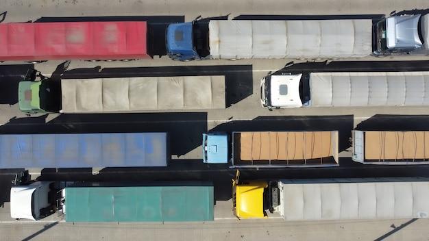 Вид сверху грузовиков с загруженным зерном в контейнерах.