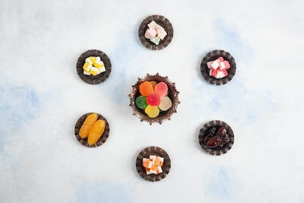 Вид сверху рахат-лукума на белой поверхности. конфеты, лукум и финики