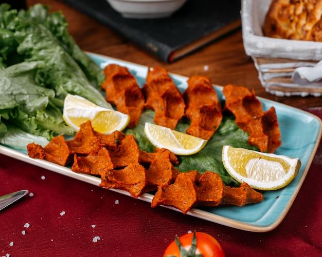 木製のテーブルにレモンとレタスのトルコ料理cig kofteのトップビュー