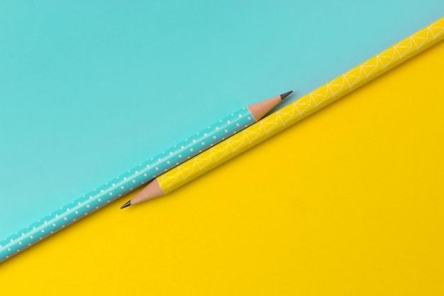 다채로운 창조적 인 종이 테이블에 청록색과 노란색 연필의 상위 뷰