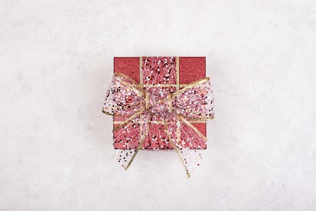Вид сверху бирюзовой изолированной подарочной коробке с белой лентой на белом фоне
