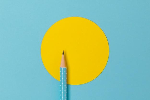다채로운 종이에 청록색 폴카 도트 연필의 상위 뷰 노란색 동그라미와 결합