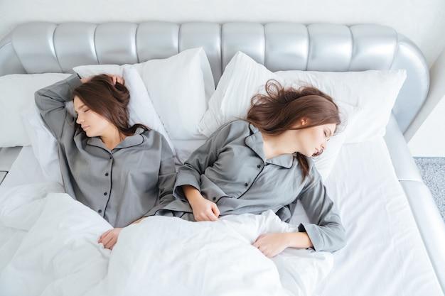Вид сверху двух привлекательных молодых сестер-близнецов, спящих в постели