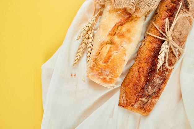 Вид сверху двух багетных хлеба на желтой поверхности