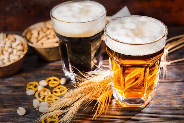 小麦の近くに注ぎたての濃いビールと明るいビール、散らばった小さなプレッツェルとピスタチオが暗い木製の机の上にある2つの大きなグラスの上面図。食品および飲料の概念