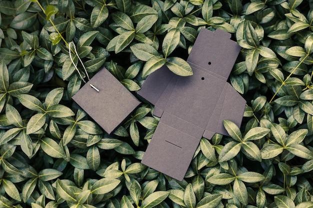배경에 있는 액세서리 또는 태그를 위한 두 개의 검은색 비어 있고 접힌 상자의 상단 보기...