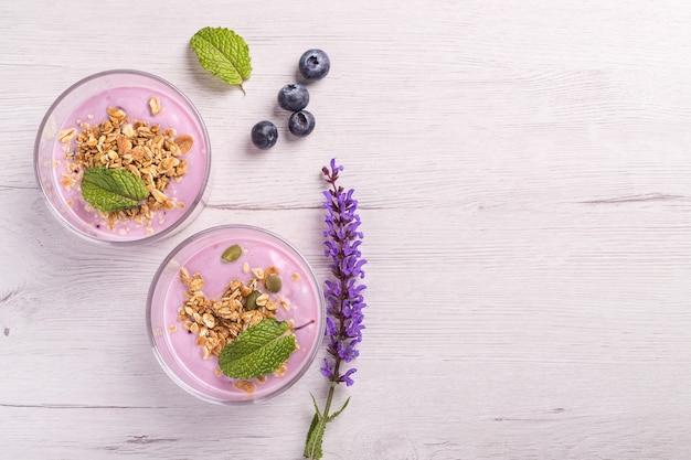 Вид сверху на две миски ягодного йогурта с мюсли и овсянкой для здорового завтрака на деревенском белом столе