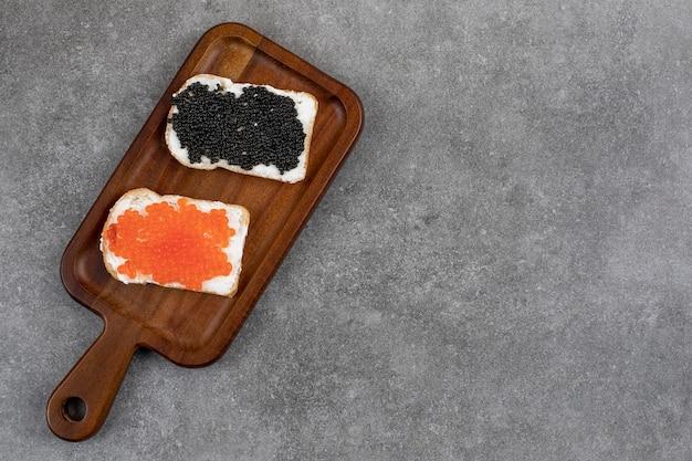 Вид сверху двух ломтиков хлеба со свежей икрой. вид сверху