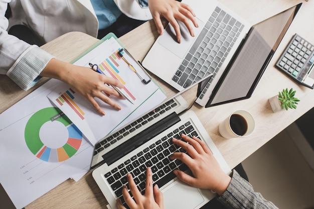 オフィスの机の上でラップトップで作業している2人のビジネス女性の上面図