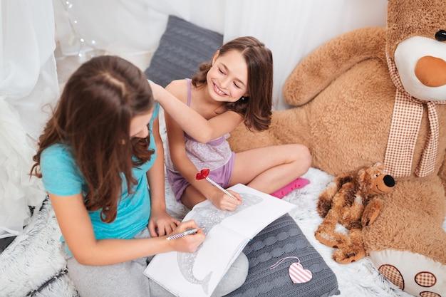 Вид сверху двух веселых очаровательных сестер, сидящих и раскрашивающих в игровой у себя дома
