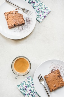 白い素朴なブラウニーケーキと2つのデザートプレートの平面図です。