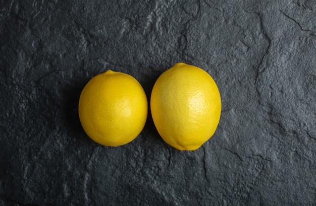 黒の背景に2つの新鮮な熟したレモンの上面図