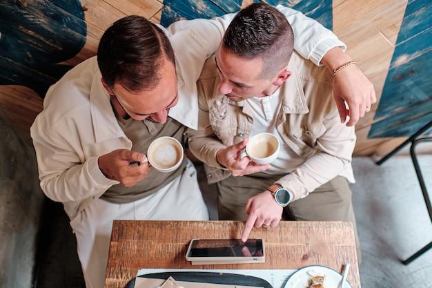 Вид сверху на двух геев в кафе, пьющих кофе с помощью планшета