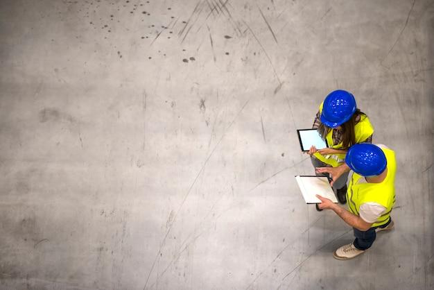 Вид сверху двух промышленных рабочих в касках и светоотражающих куртках, держащих планшет и контрольный список на сером бетонном полу