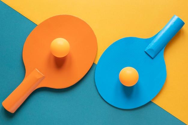 Вид сверху на две ракетки для пинг-понга с новыми шариками