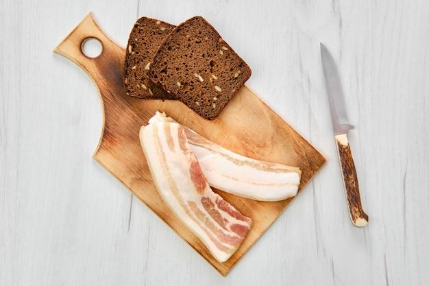 Вид сверху двух кусочков бекона и черного хлеба на деревянной разделочной доске