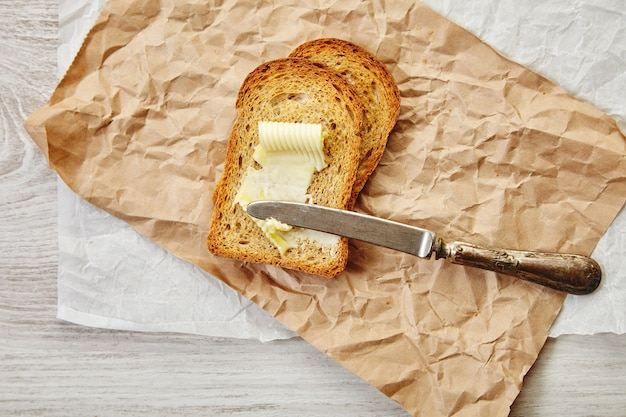 Вид сверху двух ломтиков ржаного сухого хлеба как тост с маслом на завтрак со старинным ножом на нем. все на крафтовой бумаге.